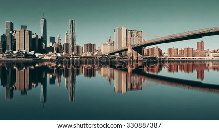 Manhattan financial district with skyscrapers and Brooklyn Bridge reflections. - stock photo