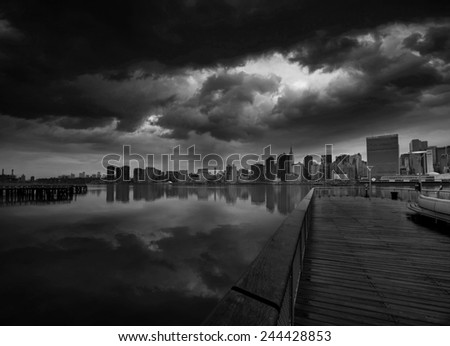 Manhattan New York cloudy dramatic skyline sunset from East River dusk USA - stock photo