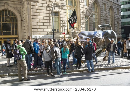 Manhattan, NYC - November 3: Tourists gathered around the Charging Bull attraction in Lower Manhattan, NYC on November 3, 2014. - stock photo