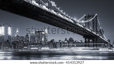 Manhattan Skyline and Manhattan Bridge At Night. Manhattan Bridge is a suspension bridge that crosses the East River in New York City. Long exposure for night image. - stock photo