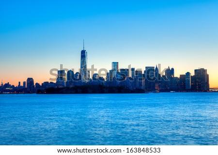 Manhattan skyline silhouette at sunrise, with Ellis Island in foreground. - stock photo