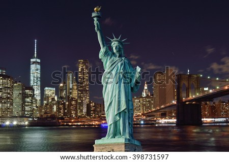 Manhattan skyline with Brooklyn Bridge at night and Statue of Liberty. - stock photo