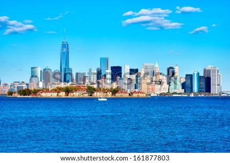 Manhattan skyline with Ellis Island in foreground. - stock photo