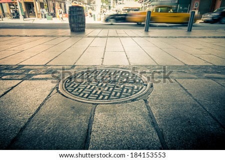 Manhole drain cover on streets of lower Manhattan - stock photo