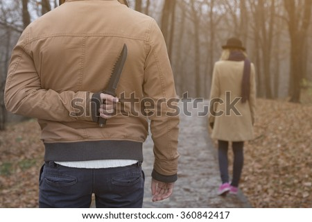Maniac and innocent victim in the park  - stock photo
