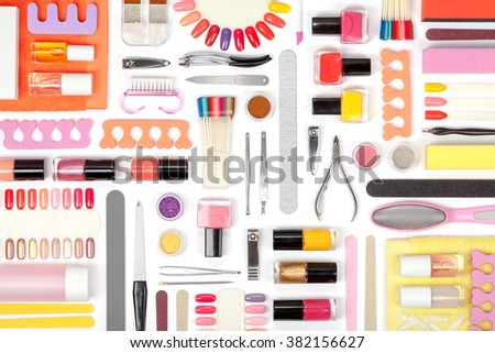 manicure and pedicure tools and other essentials on white background top view. flat lay composition in pink, orange and yellow colors - stock photo
