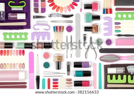 manicure and pedicure tools and other essentials on white background top view. flat lay composition in pink, violet and green colors - stock photo
