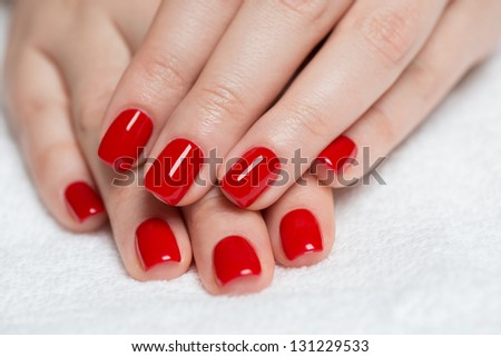 Manicure - Beautiful manicured woman's hands with red nail polish on soft white towel. - stock photo