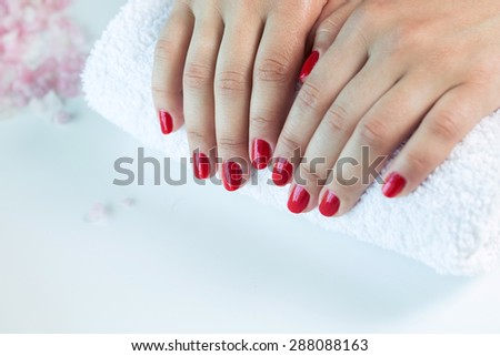 Manicure - Beautiful manicured woman's hands with red nail polish on soft white towel - stock photo
