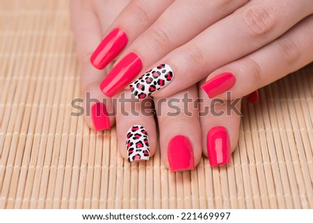 Manicure - Beautifully manicured woman fingernails. Feminine nail art with interesting animal print nail art. Selective focus on finger with leopard print. - stock photo
