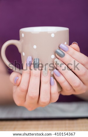 Manicure - Beauty photo of nice manicured woman fingernails holding a cup. Very nice feminine nail art with nice purple,silver and grayish nail polish. Selective focus. - stock photo