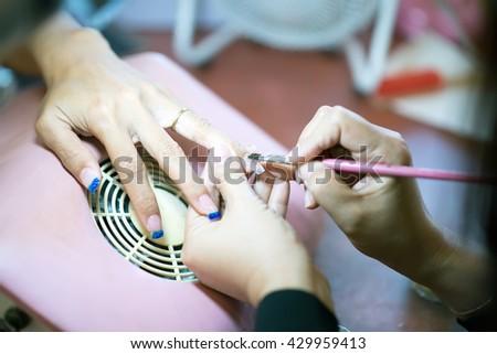 Manicure. Beauty saloon. Close-up.Apply  nail tone blur - stock photo