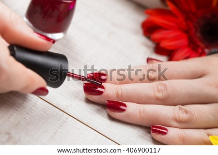Manicure - Beauty treatment photo of nice manicured woman fingernails on a white wooden desk decorated with flowers. Selective focus. - stock photo