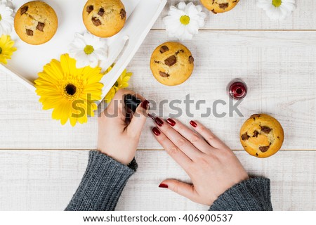 Manicure - Beauty treatment photo of nice manicured woman fingernails on a white wooden desk decorated with homemade chocolate chip muffins and flowers. - stock photo