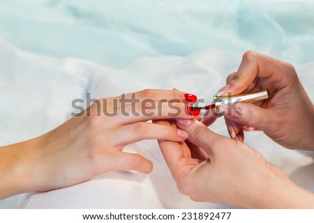 Manicure in the spa salon. Drawing of red nail polish. Spa manicure, nail care. Girl does a manicure. The concept of hand care. - stock photo