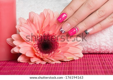 Manicure - Nice manicured woman fingernails with very interesting nail design touching flower. - stock photo