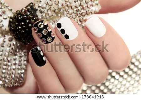 Manicure on short nails covered with black and white lacquered with rhinestones on a black background  - stock photo