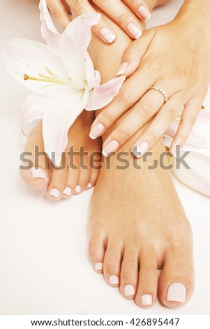 manicure pedicure with flower lily close up isolated on white perfect shape hands spa salon - stock photo
