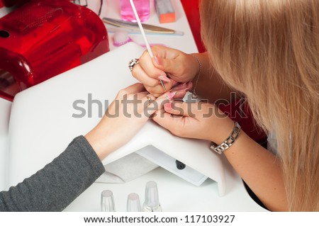 Manicure process in beauty salon showing coloring and drawing on artificial nails. - stock photo
