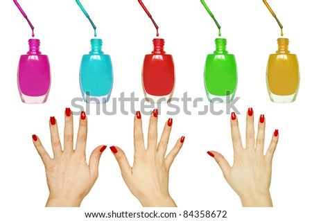 Manicure set - Beautiful red manicured woman hands and colorful nail polishes isolated on white - stock photo