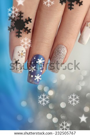 Manicure with snowflakes on your nails with colored lacquers on a rectangular shaped nails. - stock photo