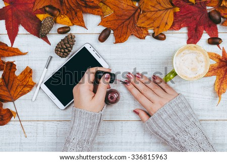 Manicure - Woman having manicure on a white wooden table decorated with leaves.  - stock photo