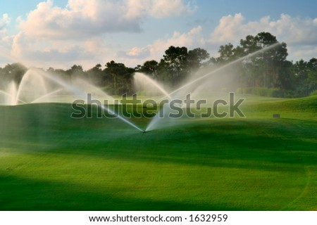manicured florida golf course gets irrigated in morning - stock photo