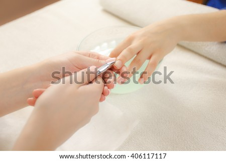Manicurist clear cuticle professional scissors for manicure and pedicure. Manicure process in a beauty salon. - stock photo