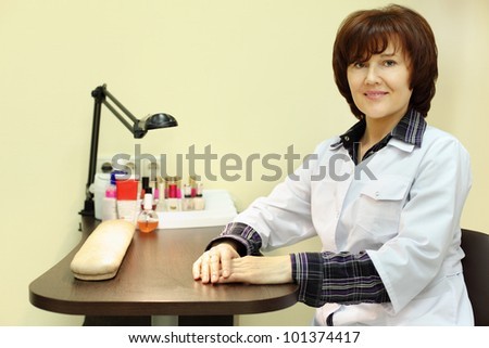 Manicurist dressed in white robe sits at table for manicure in beauty salon - stock photo