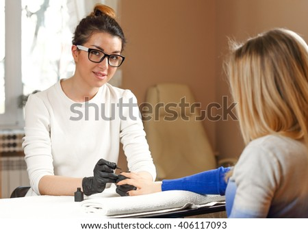 Manicurist looks at the camera and smiling. Portrait of a beautiful professional manicure and pedicure master. - stock photo