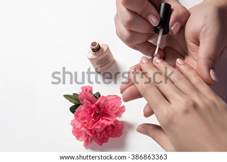 manicurist paints nails to a customer. Care for hands. Specialist, after performing a hardware manicure without nail Polish beige. - stock photo