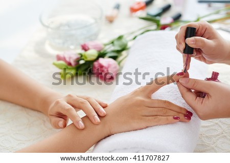Manicurist polishing fingernails with marsala color - stock photo