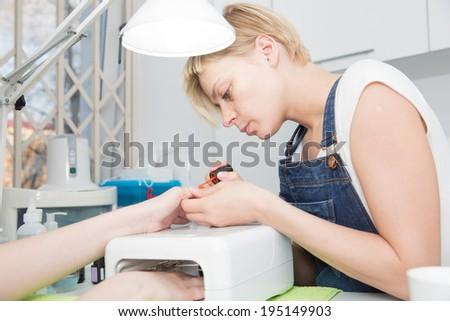manicurists paints  nails under  lamp - stock photo