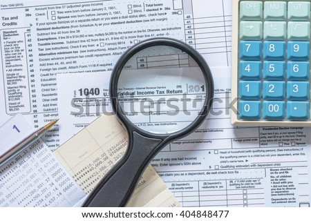 Manifier glass looking at text heading of US Income tax return empty blank paper form for American residents with blur calculator and bank book record background: USA Tax day concept - stock photo