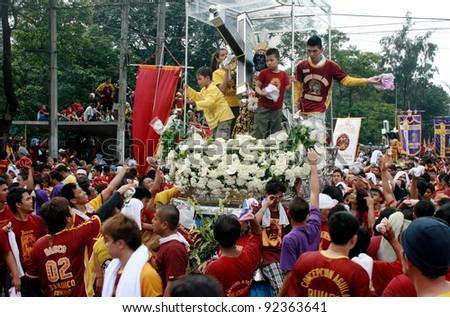 MANILA - JAN. 9: Devotees celebrate the feast of The Black Nazarene on January 9, 2012 in Manila Philippines. Image of the Black Nazarene procession around the city. - stock photo
