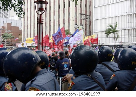 MANILA, PHILIPPINES- JUNE 12: Police stops the protester at The Philippines Independence day on June 12, 2014 in Manila. The Philippines celebrate the 116th Independence Day. - stock photo