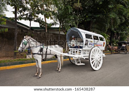 MANILA, PHILIPPINES - MARCH 18: Horse with carriage in Intramuros on March, 18, 2013, Manila, Philippines. Intramuros is the oldest district and historic core of Manila,  capital of the Philippines. - stock photo