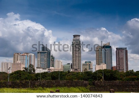 Manila's cityscape view from Baluarte de San Diego the circular fort one of the oldest stone fortifications on Intramuros district of Manila, Philippines. - stock photo