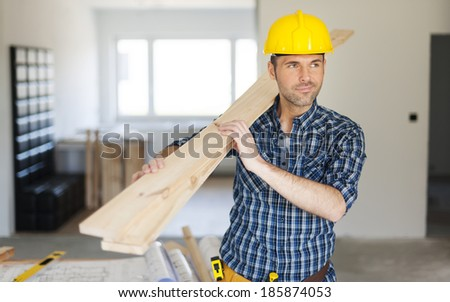 Manley construction worker holding wood planks - stock photo