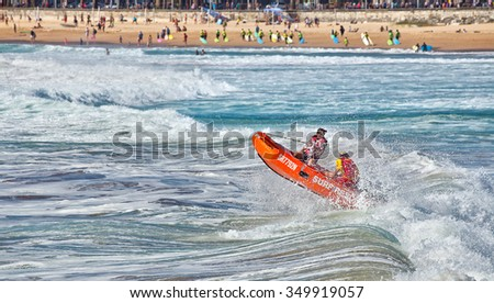MANLY,AUSTRALIA - DECEMBER 6,2015: Surf lifesavers guide their dinghy out from the beach into heavy surf. Surf Lifesaving Australia has over 300,000 members - mostly volunteers. - stock photo
