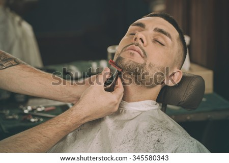 Manly beauty day. Cropped closeup of a young man having his beard shaped in a barbershop - stock photo