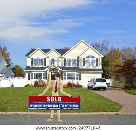 Mannequin wearing red tie holding Real estate sold (another success let us help you buy sell your next home) sign Suburban McMansion home autumn day blue sky residential neighborhood USA - stock photo