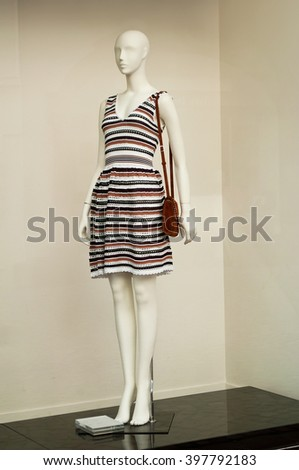 mannequin with dress in a fashion showroom for women - stock photo
