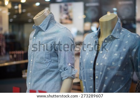 Mannequins in blue jeans shirts with patterns in clothes store - stock photo