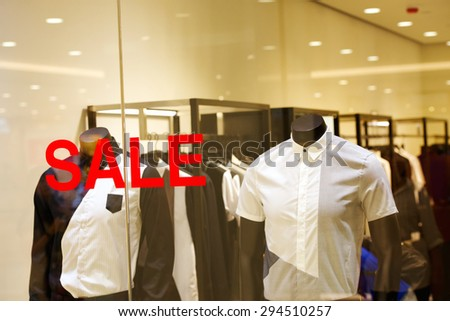 Mannequins in the store window, on window Sale sticker. - stock photo