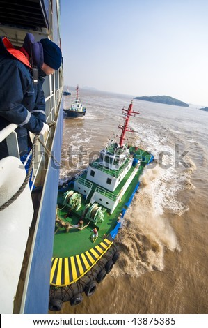 manoeuvring with tug boats. huge container ship - stock photo