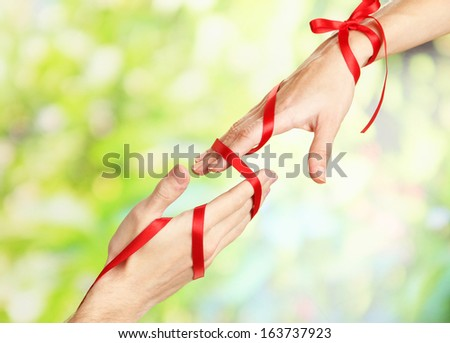 Mans and girls hands tied with ribbon on bright background - stock photo