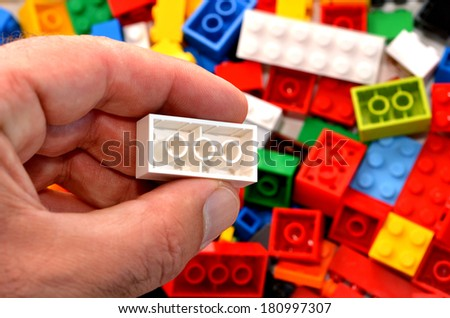 Mans hand holds a red toy block against mix of building blocks background. concept photo of imagination, creativity, planning and ideas - stock photo
