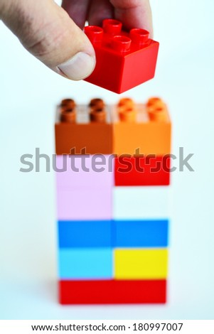 Mans hand puts a red toy block on top of a building blocks tower in the background. concept photo of imagination, creativity, planning and ideas - stock photo