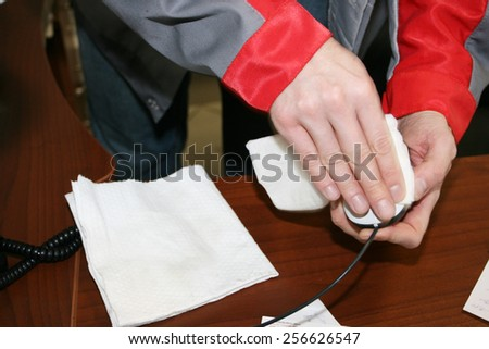 Mans hands cleaning up a computer mouse in office - stock photo